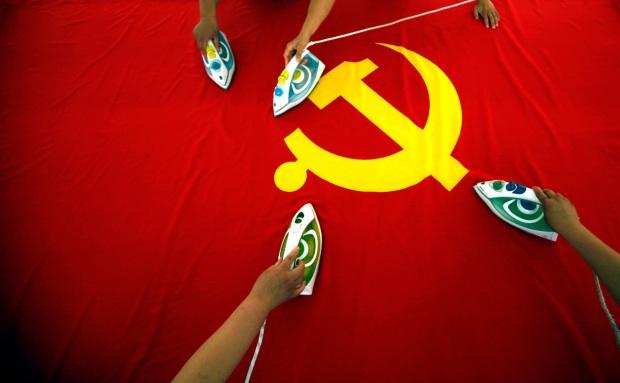 Impiegati che stirano una bandiera comunista prima di una manifestazione in Cina (foto via @chinatoday)