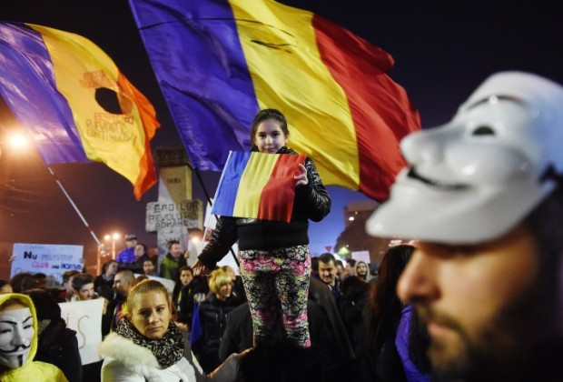 Protesters hold flags as they demonstrate against the political class and Romanian authorities during the third day of protest in Bucharest on November 5, 2015. Romania's president on November 5, 2015, appointed Education Minister Sorin Campeanu as interim prime minister to replace Victor Ponta, who quit following mass anti-government protests sparked by a deadly nightclub fire. The wave of discontent has roots going back to Romania's emergence from Soviet rule in the 1990s and its struggle to shrug off endemic corruption.  AFP PHOTO / DANIEL MIHAILESCU        (Photo credit should read DANIEL MIHAILESCU/AFP/Getty Images)