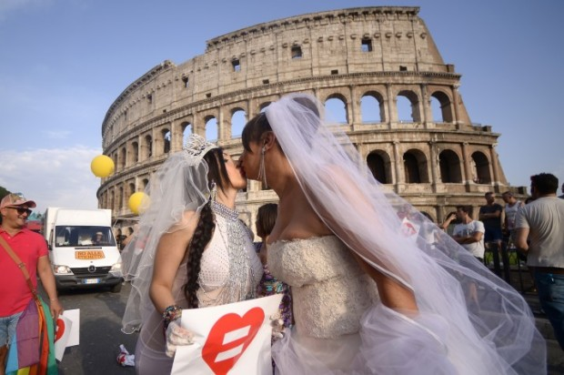 Brides kiss near the Colosseum during the Gay Pride Parade (LGBT) on June 13, 2015 in Rome.  AFP PHOTO / FILIPPO MONTEFORTE        (Photo credit should read FILIPPO MONTEFORTE/AFP/Getty Images)